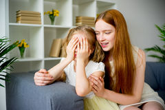 Mother comforting daughter. Mother comforting her teenage daughter at home Stock Image