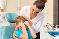 Mother comforting her son. Caring mother comforting her son in dentist office Stock Images
