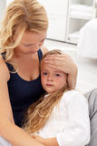 Mother comforting her upset kid. Mother comforting her upset or sick little girl Royalty Free Stock Photography