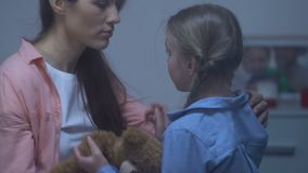 Mother comforting little sad daughter holding teddy bear, parental support, care. Stock footage stock video footage