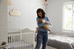 Mother Comforting Newborn Baby Son In Nursery Stock Image