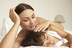 Mother Comforting Sleeping Son In Bed Stock Image