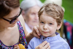 Mother comforting son after falling down and hurting face. During walk in park. Boy eating cookie, senior grandmother sitting beside on bench Stock Photography