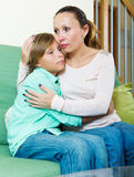 Mother comforting teenage boy. On sofa at home Stock Photos