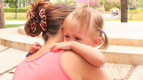 Mother comforts crying little daughter with hairtails in park stock video footage