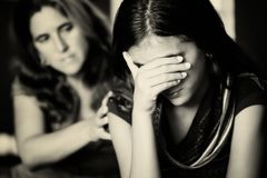 Mother comforts her crying teenage daughter stock image