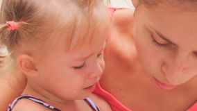 mother comforts kisses crying little daughter with hairtails stock footage