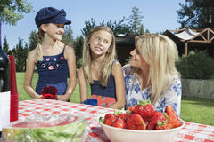 Mother communicating with daughters while sitting at outdoor dining table Stock Photo