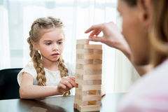 Mother and concentrated little daughter playing jenga game Royalty Free Stock Images