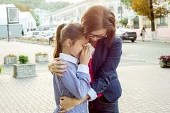 Mother consoling her crying daughter. Urban background. royalty free stock images