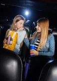 Mother Consoling Scared Daughter In Cinema Theater. Mother consoling scared daughter while watching movie in cinema theater stock image