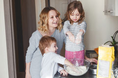 Mother cooking with children Stock Images
