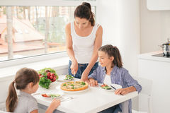 Mother cooking healthy meal for children Stock Photos