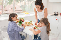 Mother cooking healthy meal for children Royalty Free Stock Photos