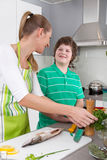 Mother cooking with her son in the kitchen - family life. Preparing fresh fish - mother cooking with her son in the kitchen - family life royalty free stock photo