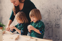 Mother cooking with kids in kitchen. Toddler siblings baking together and playing with pastry at home Royalty Free Stock Images
