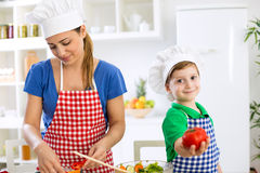 Mother cooking lunch and little cute boy holding tomato Royalty Free Stock Photography