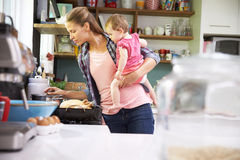 Mother Cooking Meal Whilst Holding Daughter In Kitchen Stock Photos