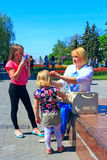 Mother corrects her daughter`s hair during a walk through the spring town Stock Photo
