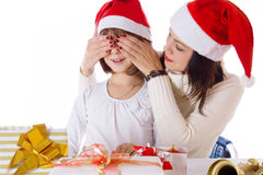 Mother covering daughter eyes with hands hiding Christmas gifts. Over white Stock Image
