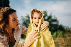 mother covering daughter with towel after swimming royalty free stock images
