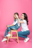 Mother covering eyes to cute smiling daughter sitting on stool Stock Photography