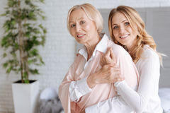 Mother covering her daughters hand embracing her. Never let you go. Elegant senior women covering the hand of her daughter with her own one while the daughter Royalty Free Stock Photo