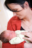 Mother cradling baby girl. Portrait of young mother cradling sleeping newborn baby girl Stock Photos