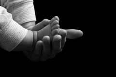 Mother cradling the feet of her newborn baby. Monochrome image of a loving mother tenderly cradling the feet of her newborn baby in her hand Royalty Free Stock Photography