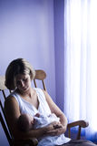 Mother cradling newborn. Mother rocking newborn baby in rocking chair next to window Stock Photo