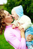 Mother and crying baby. Young beautiful mother and her crying baby outdoor in the park in summertime Stock Photo