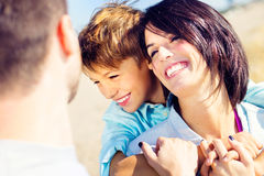 Mother cuddles her son while father watches them moved. In front of the sea Stock Photos