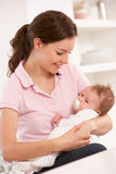 Mother Cuddling Baby Boy At Home Stock Image