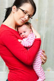 Mother cuddling baby girl. Half body portrait of young mother cuddling baby girl indoors Royalty Free Stock Photos
