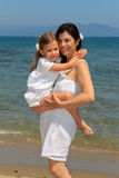 Mother cuddling daughter on a beach Stock Images