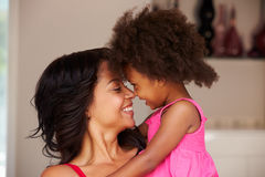 Mother Cuddling Daughter At Home Stock Image