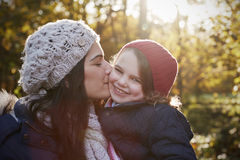 Mother Cuddling Daughter On Walk In Autumn Countryside Stock Image