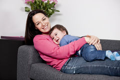 A mother cuddling her baby son on a sofa Royalty Free Stock Image