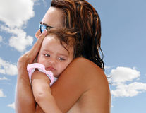 Mother cuddling small girl. A profile view of a mother lovingly holding a small girl with clouds and sky in the background Royalty Free Stock Image
