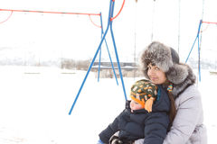 Mother cuddling a tired little boy in snow. Smiling mother cuddling a tired little boy sitting outdoors on a cold winters day in a snowcovered childrens Stock Image