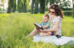 Mother with curly hairstyle reading fairy tales for baby Stock Image
