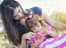 Mother and Cute Baby Daughter Playing with Cell Phone Royalty Free Stock Images