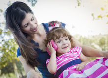 Mother and Cute Baby Daughter Playing with Cell Phone Royalty Free Stock Photography