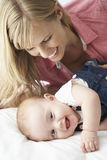 Mother With Cute Baby Girl Playing On Bed Stock Photos