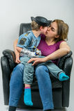 Mother and cute child dressed in pirate and police costume sitting in black armchair. Mother giving her son a kiss. Stock Photos