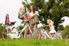 Mother with cute daughters cycling at meadow. Portrait of happy young women with cute daughters cycling at meadow stock photography
