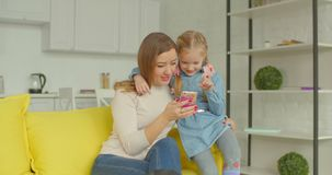 Mother and cute girl browsing online on cellphone stock footage