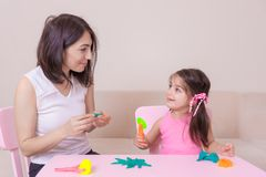 Mother and Cute girl playing together with playdough royalty free stock photography
