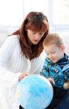 Mother and cute kid studying globe together. Mother and cute little kid studying globe together at home Royalty Free Stock Photos