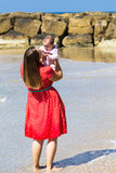 Mother and cute little baby girl on the beach Stock Image